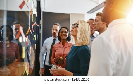 Young businesswoman and her team brainstorming with sticky notes on a glass wall while working together in a modern office