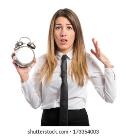 Young businesswoman holding an antique clock over white background