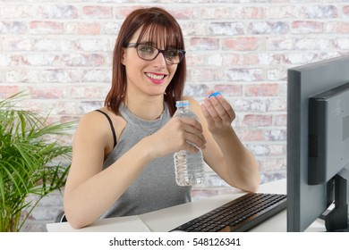 Young businesswoman holding a bottle of water in office