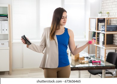 Young Businesswoman Holding Calculator Exercising With Dumbbells In Office