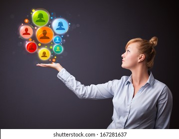 Young businesswoman holding colorful social network icons in her hand