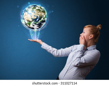 Young businesswoman holding in her hand a glowing earth globe, Elements of this image furnished by NASA