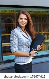 Young businesswoman holding a pen and folder with papers