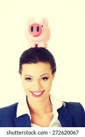 Young businesswoman holding a piggybank on head