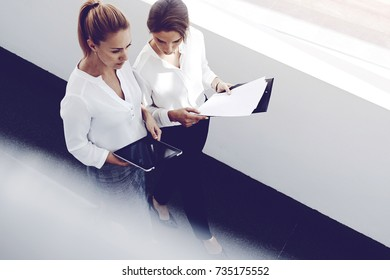 Young businesswoman is holding portable touch pad, while her secretary near is walking with paper documents in hands. Female lawyer is using with partner digital tablet for preparing to briefing