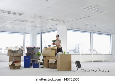 Young businesswoman holding potted plant near cartons and equipment in empty office space