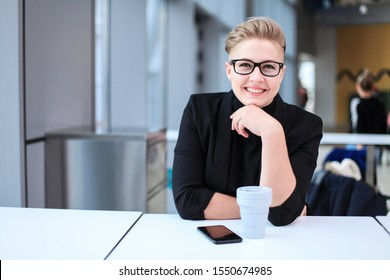 Young businesswoman holding a silicone collapsible cup, reusable coffee tumbler, talking on a smartphone. Wearing glasses, short hairstyle