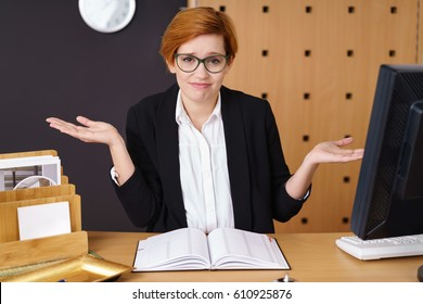 Young businesswoman or hotel receptionist shrugging her shoulders and raising her hands in the air to show her ignorance or that she does not care