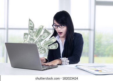 Young businesswoman with laptop and money in great online business