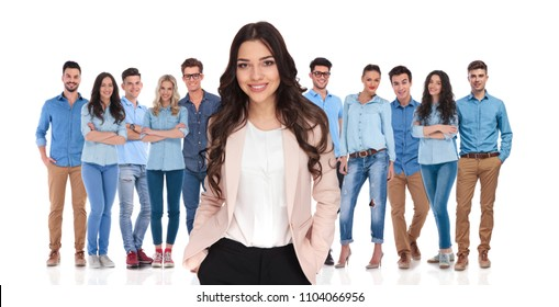 young businesswoman leader relaxing with her casual team with hands in pockets after a productive day of work. They are standing on a white background