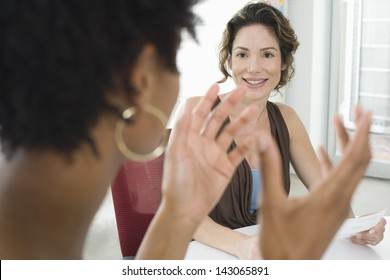 Young businesswoman listening to female colleague during meeting in office