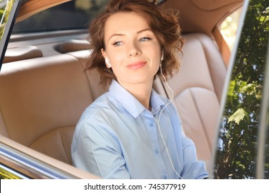Young businesswoman listening to music on back seat of a car