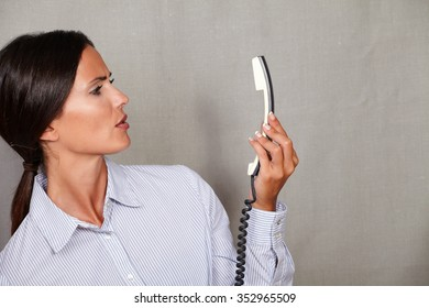 Young businesswoman looking angry at the phone without speaking on grey texture background