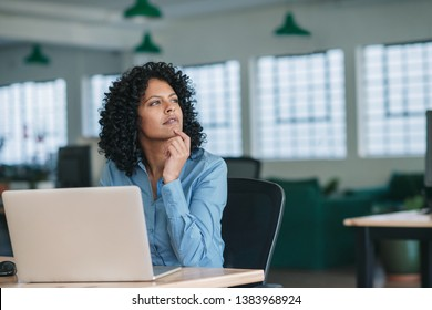 Young businesswoman looking deep in thought while sitting at her desk in a large modern office working online with a laptop