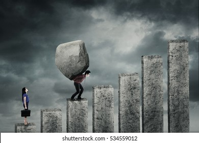 Young businesswoman looking at her partner carrying a big boulder while walking upward on the graph