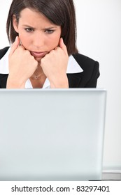 young businesswoman looking worried in front of laptop