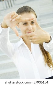 Young businesswoman looks through a frame made of hand