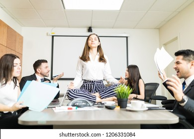 Young businesswoman meditating in lotus position while colleagues yelling during negotiation in office