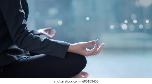 Young businesswoman meditating in office
