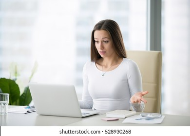 Young businesswoman at the modern office desk with laptop puzzled by a private photo posted, result of election, salary, world currency exchange rates, can not believe her eyes