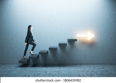 Young businesswoman moving up on stairs with arrow on gray wall. Leadership and career development concept.