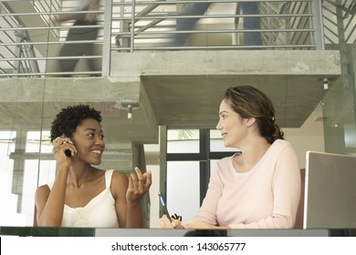Young businesswoman on call with female colleague noting down at table