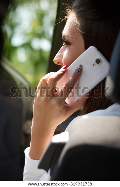 Young businesswoman on the phone in her car