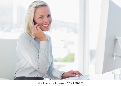 Young businesswoman on the phone smiling at camera at her desk