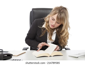 Young businesswoman paging through a book at her desk as she tries to find the answer to a problem or locate specific information