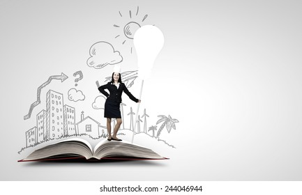 Young businesswoman in paper crown standing on book