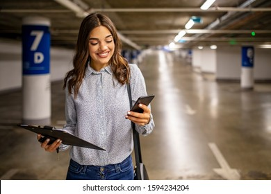 Young businesswoman in a parking garage, using a mobile app. About 20 years old, Caucasian female. Elegant woman using smartphone in parking garage, holding clipboard