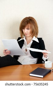 Young businesswoman reading document at office
