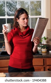 Young businesswoman reading the newspaper holding a cup