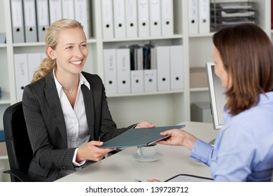 Young businesswoman receiving application file from candidate at office desk
