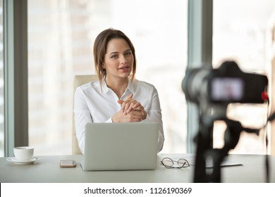 Young businesswoman recording vlog talking to camera in office, successful female business trainer coach filming live video blog giving presentation speaking about online training, vlogging concept