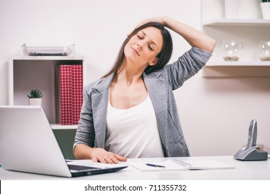 Young businesswoman is relaxing in her office. She is stretching her body.