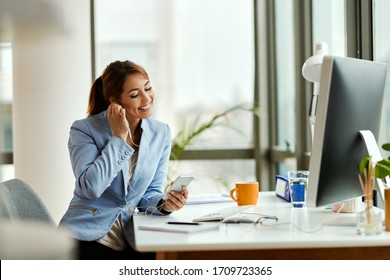 Young businesswoman relaxing while using mobile phone and listening music over earphones in the office.