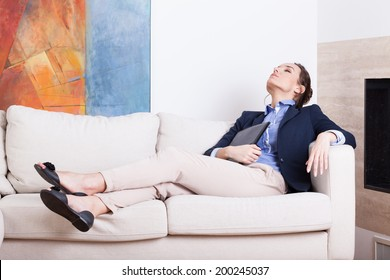 Young businesswoman resting on sofa after work