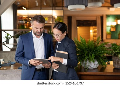 Young businesswoman scrolling through electronic form of contract in touchpad held by mature colleague at meeting
