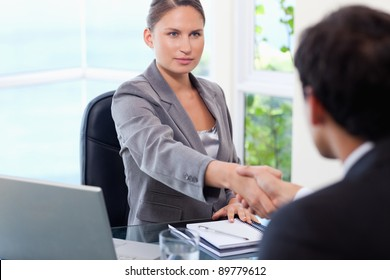 Young businesswoman shaking hands with customer