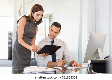 Young businesswoman sharing information with serious businessman. Young secretary showing business report to worried businessman. Formal colleagues working in modern office discussing documents.