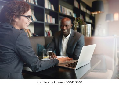 Young businesswoman showing presentation on laptop to her business partner. Happy executives in a meeting at restaurant