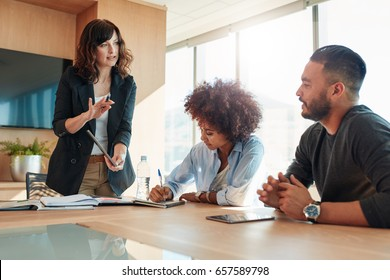 Young businesswoman showing something to her colleagues during a meeting in conference room. Multi ethnic business team discussing project in office.