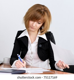 Young businesswoman signing document at office