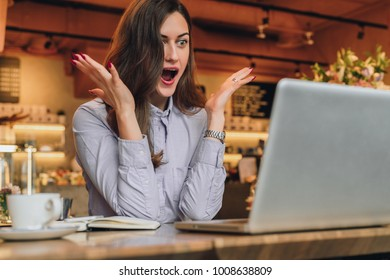 Young businesswoman is sitting in cafe at table in front of laptop and opening her mouth and raising her hands in surprise looks at screen. Girl received an email and is happy with good news.