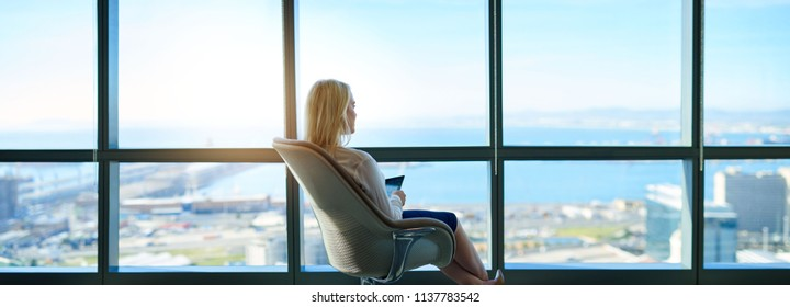 Young businesswoman sitting in a chair using a digital tablet while looking through office windows overlooking the city skyline