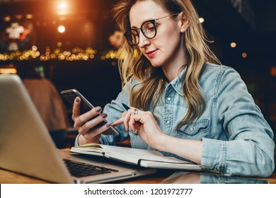 Young businesswoman is sitting in coffee shop at table in front of computer and notebook,using smartphone. Hipster girl checking e-mail, chatting, blogging. Social media, online marketing, edication.