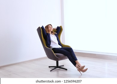 Young businesswoman sitting in comfortable armchair indoors