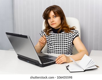 Young businesswoman sitting at a desk in office