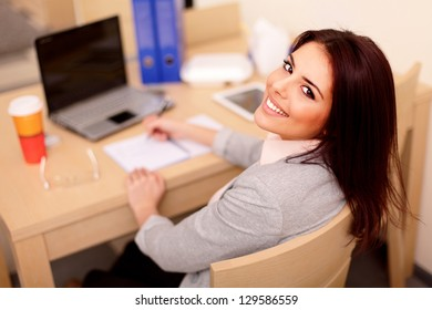 Young businesswoman sitting at desk and working. Smiling and looking back at camera